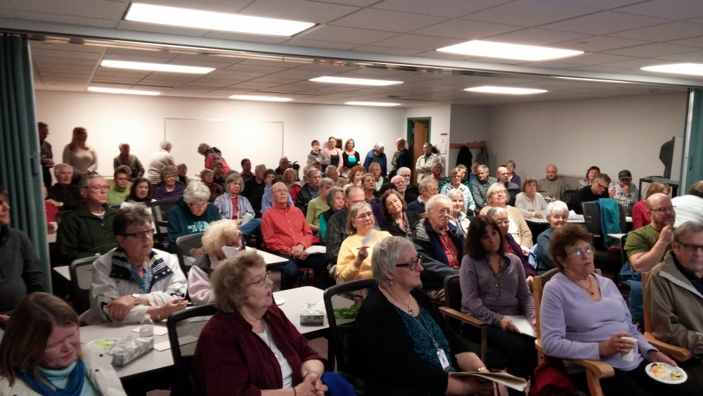 Large group gathered indoors for meeting